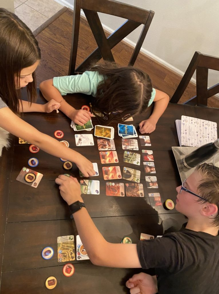 3 kids reach for gems and cards during a game of splendor