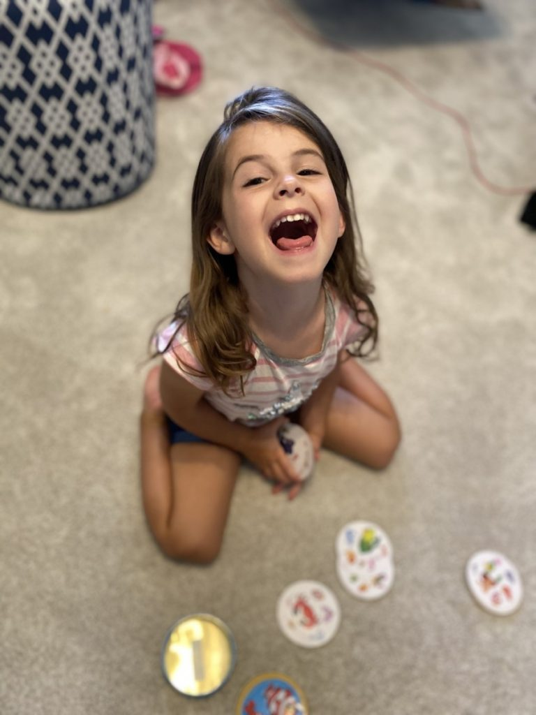 A little girls smiles big while playing spot it junior family games