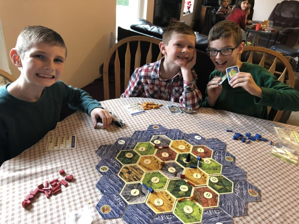 3 boys playing Settlers of Catan