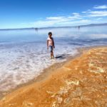 A young girls stands at the edge of the Great Salt Lake and the yellow and gold swirling sand on the beach