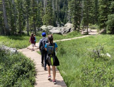 4 kids walk on a boardwalk through a field to Emerald Lake in Rocky Mountain National Park