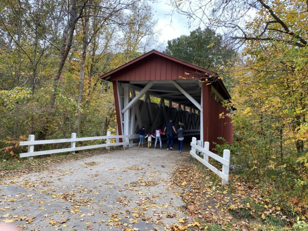 Dad and 4 kids walk into Everett Covered bridge in Cuyahoga Valley National Park