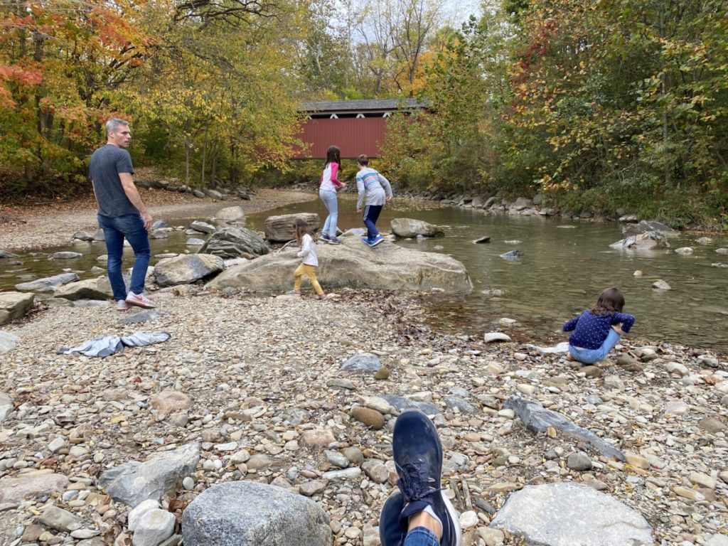 Dad and 4 kids play in the rocks under Everett's covered bridge in Cuyahoga Valley National Park