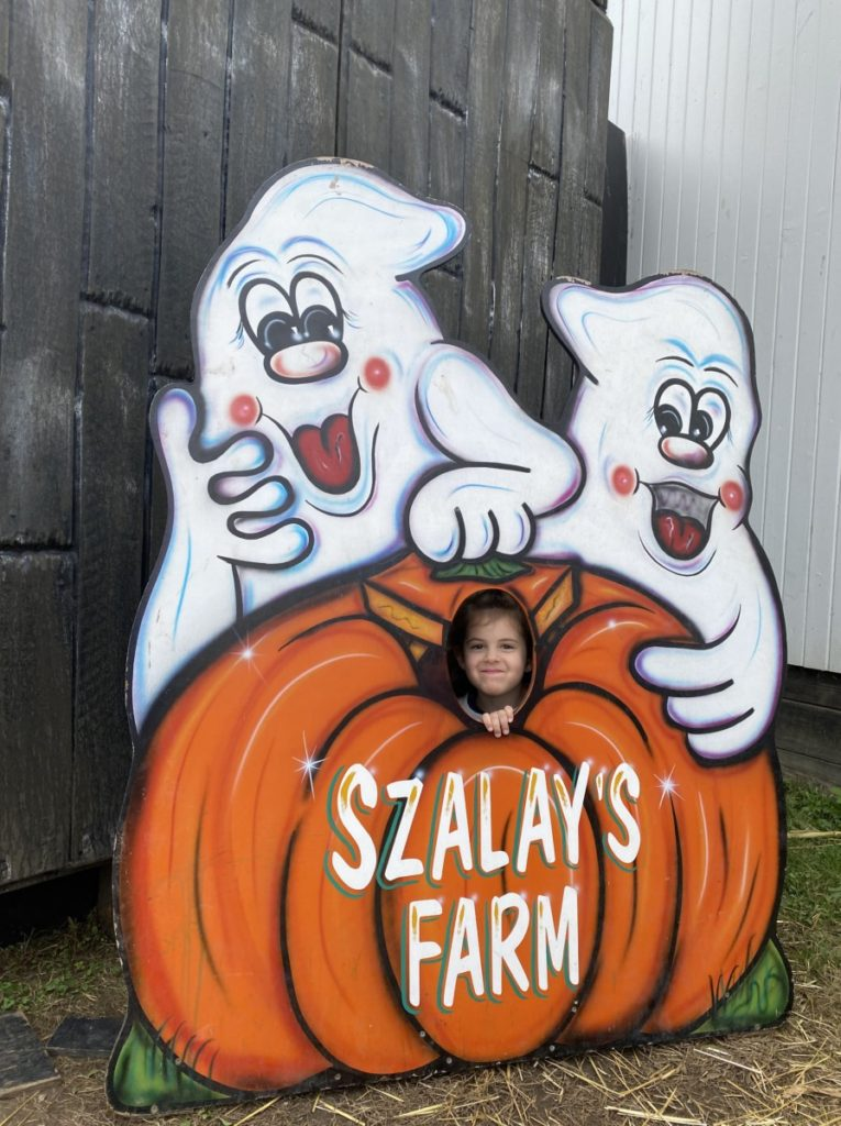 Little girl in a pumpkin cut out at Szalays Farm in Cuyahoga Valley National Park