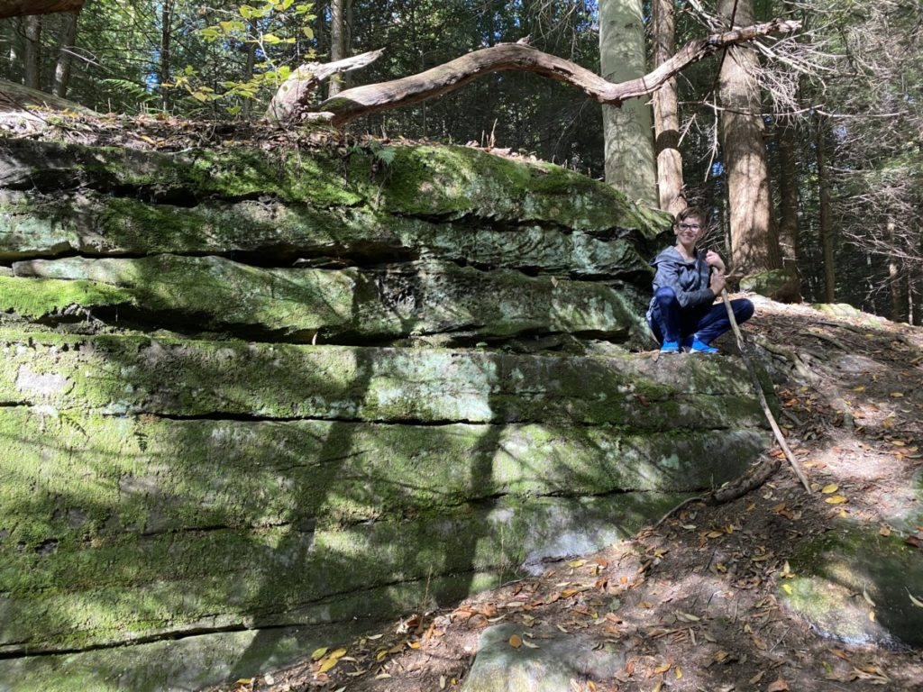 Young boy squats on the Ledges at Cuyahoga Valley National Park
