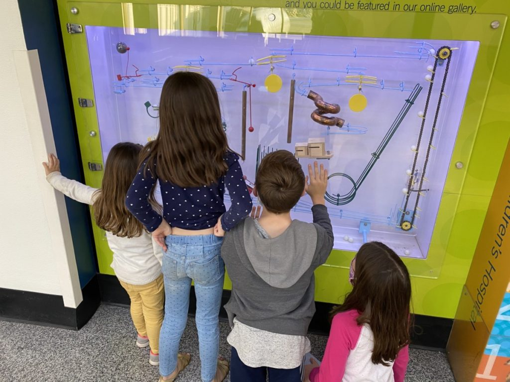 4 kids staring at Cleveland Airport ball display