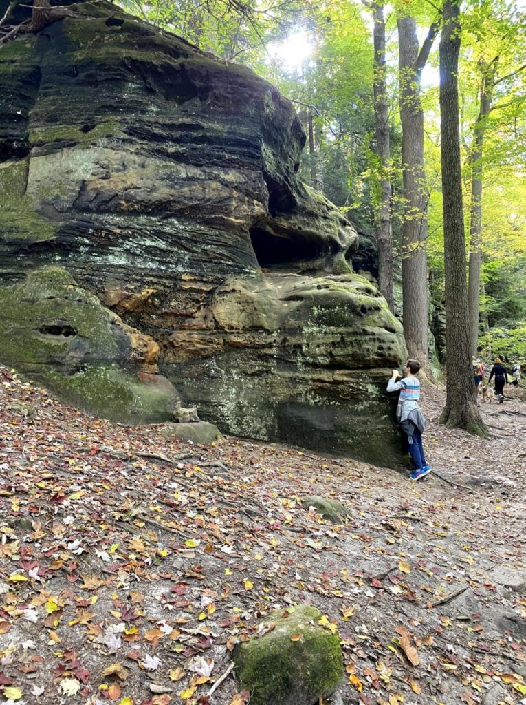 A boy hugging a rock that looks like an ape head at the ledges in Cuyahoga National Park