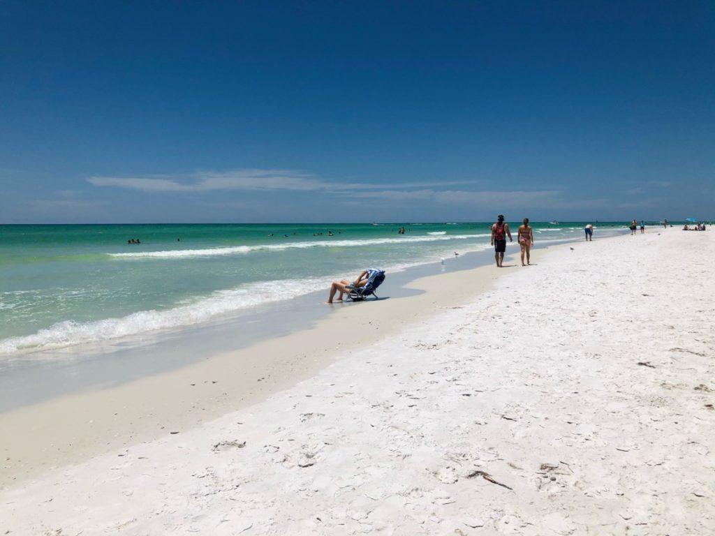 Beach goers walk and relax on Siesta Key Beach in Florida