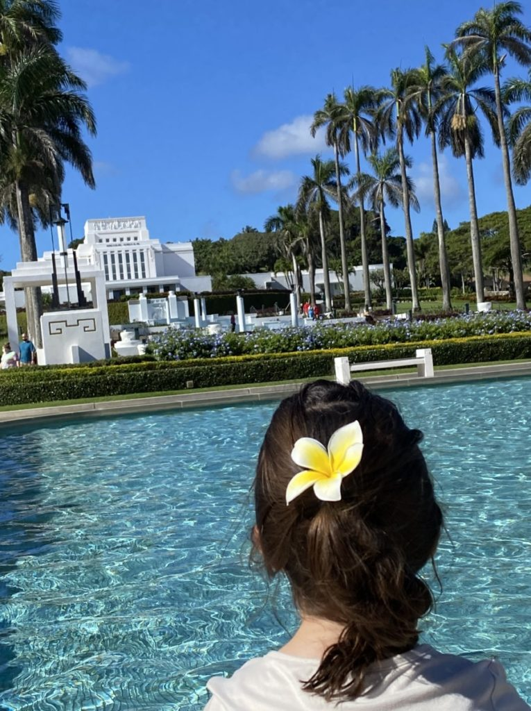 A young girls with a plumeria in her hair at the Lai'e LDS temple in Hawaii.