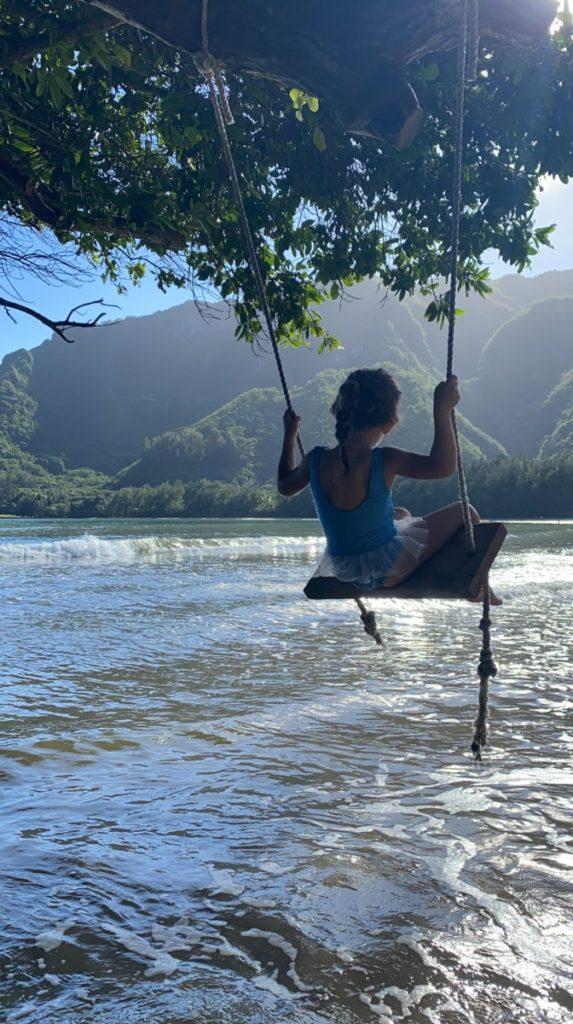 A young girl swinging at Kahana Bay Beach Park swing