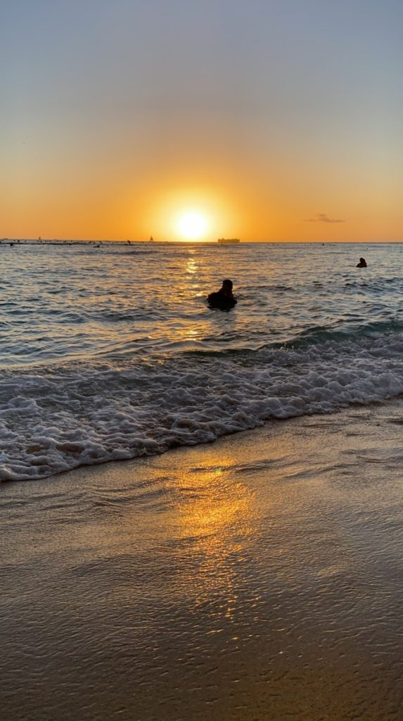 The sun on the horizon creating an orange glow sunset on Waikiki while a boogie boarder floats in the water