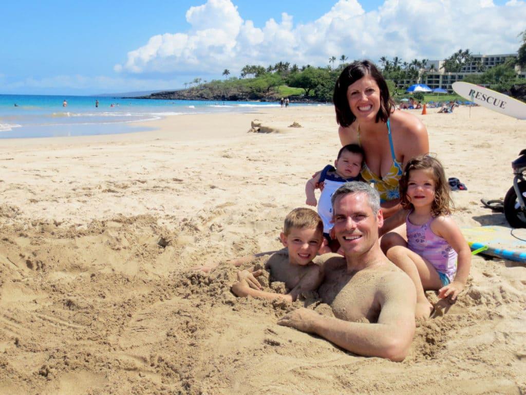A family in the sand at Hapuna Beach on Big Island, Hawaii