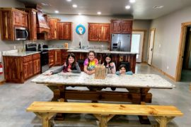 4 girls on the large dining table with the stocked kitchen at Lake Texoma Luxury Rentals